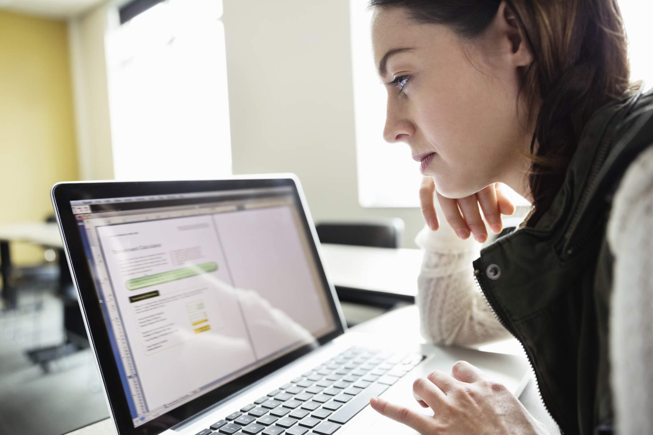 Mujer delante de pantalla de computadora.