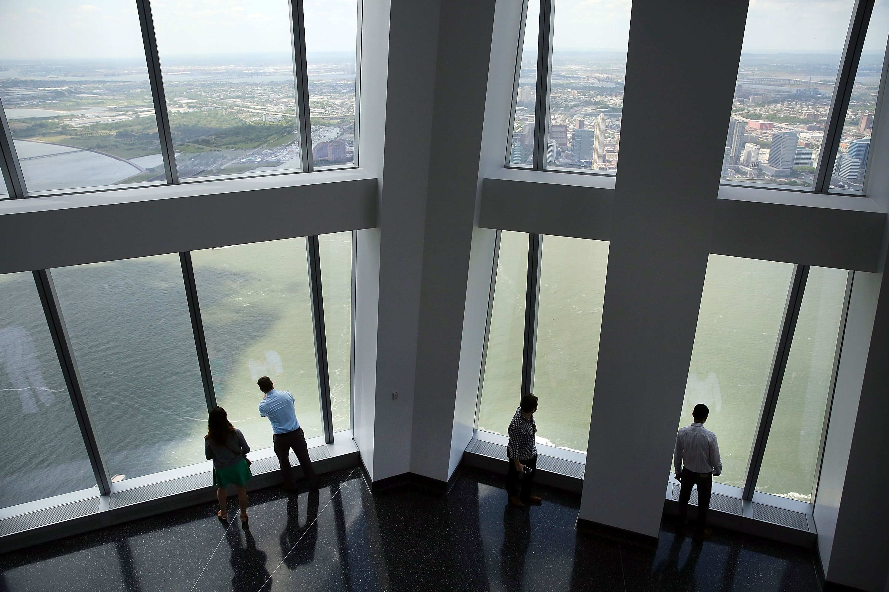 People looking out two-story windows of One World Observatory at 1WTC, open to the public