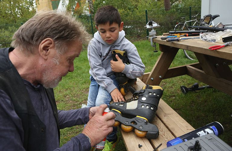 Man and child repairing Rollerblades