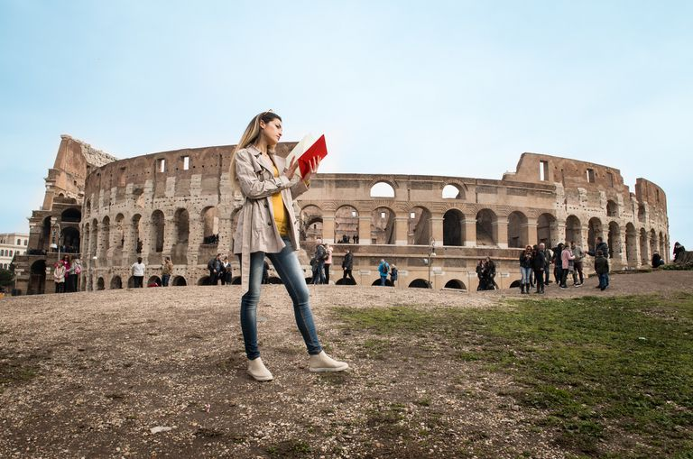 Young woman with a book in front of the Colosseum.
