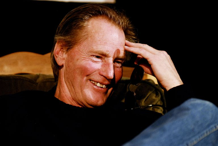 Sam Shepard in jeans and a black shirt, with his hand touching his forehead