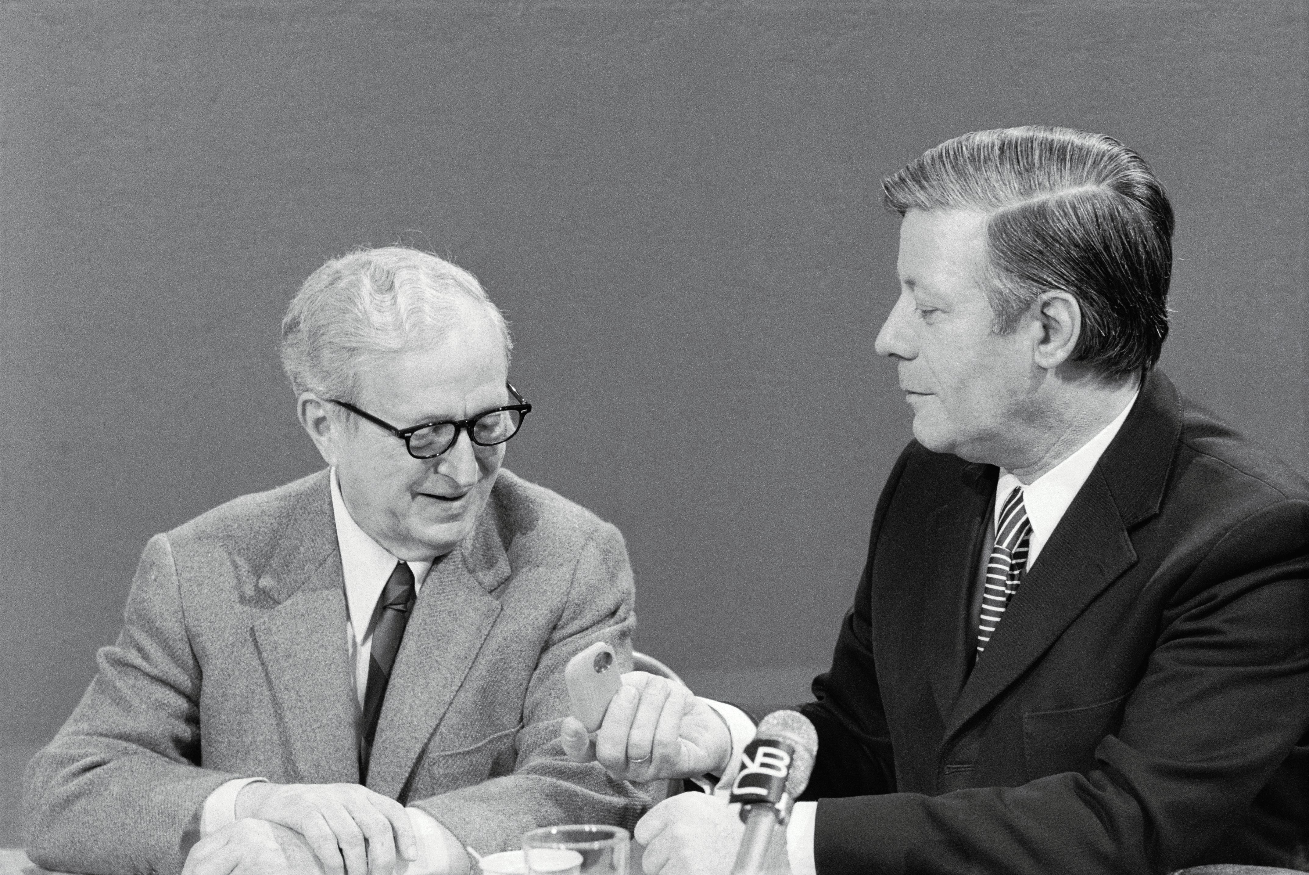 West German Chancellor Helmut Schmidt inviting Lawrence Spivak, left, to try sniffing snuff.