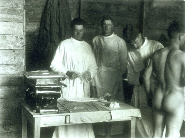 A naked man getting inoculated for influenza at an embarkation camp in France.