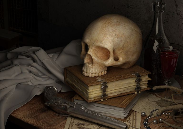 Skull sitting on top of two books on top of a treasure map next to an old pistol.