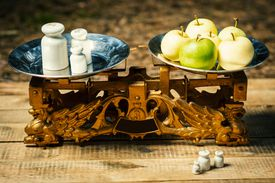 old scales painted gold with weights and green apples