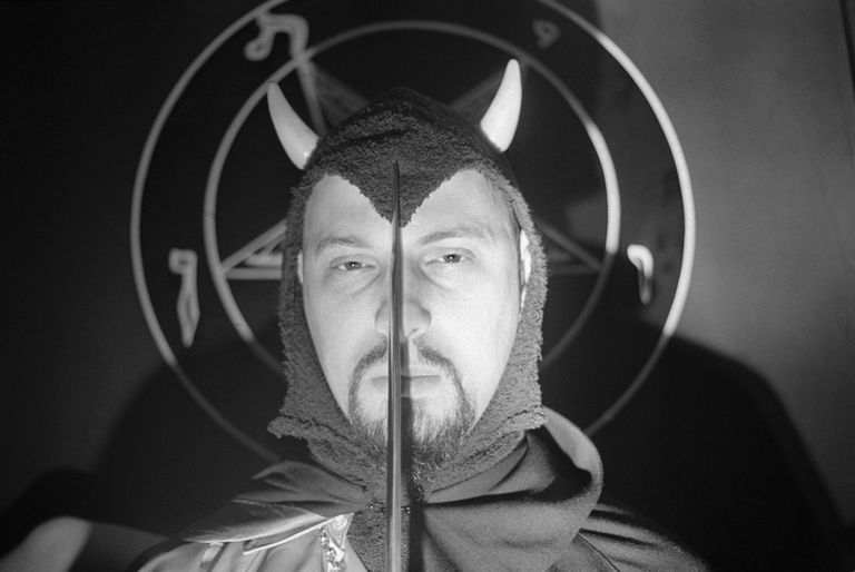 Anton LaVey in costume in front of satanism symbol holding knife over face.