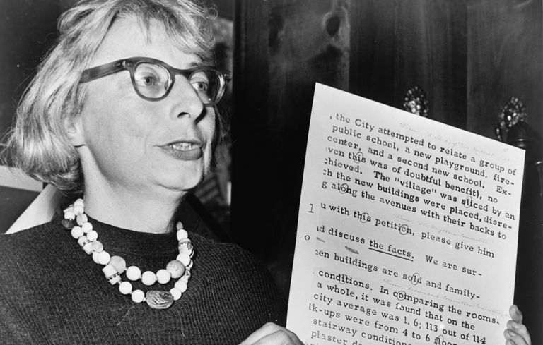 black and white historic photo of Jane Jacobs holding up a document