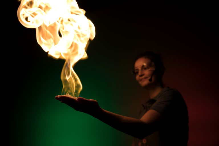 A fire demonstration in the palm of a hand performed by a professional with safety goggles in a science center