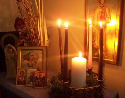 Fully lit Advent wreath with a central Christmas candle on a home altar. (Photo © Scott P. Richert)
