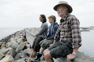 Three men on a sea wall