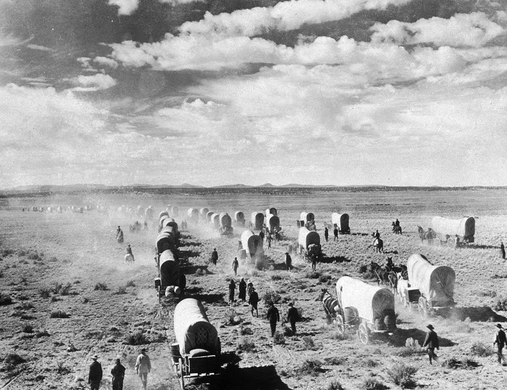 A wagon train of American homesteaders moves across the open plains
