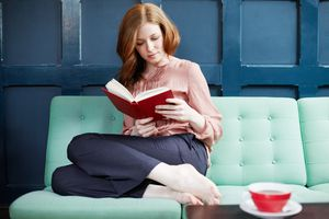 Woman reading a book on sofa.