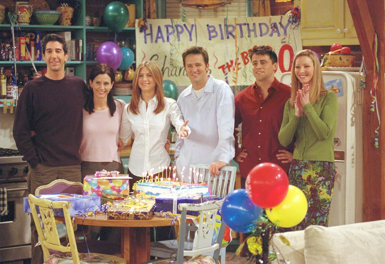 The cast of Friends posing in front of Birthday sign on set.