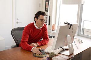 Man Sitting At Desk Using Computer