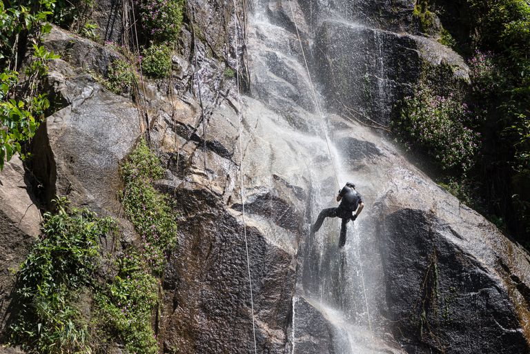A man rappelling down from waterfall, Thailand