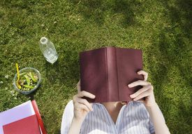 Woman reading a book outdoors on the grass