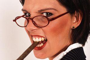 Businesswoman smoking cigar, portrait