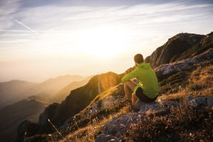 Mountain Running Man Sitting on Rock Looking at Sunset