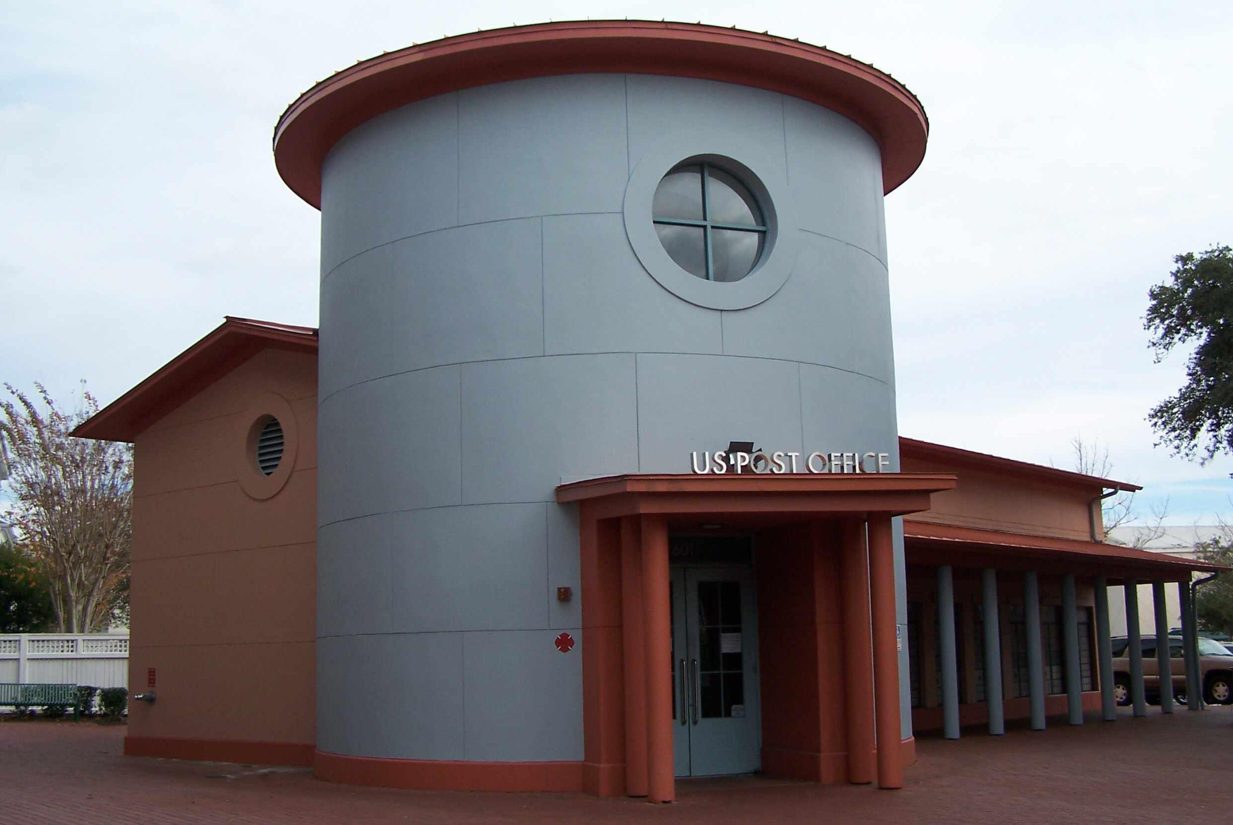 Oficina de correos azul cilíndrica con techo de cúpula roja, columnas rojas y una ventana de ojo de buey encima de la puerta