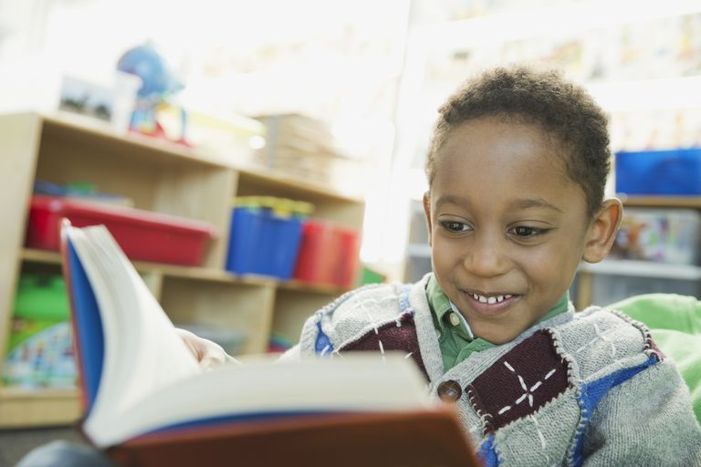 Smiling boy reading book in elementary school