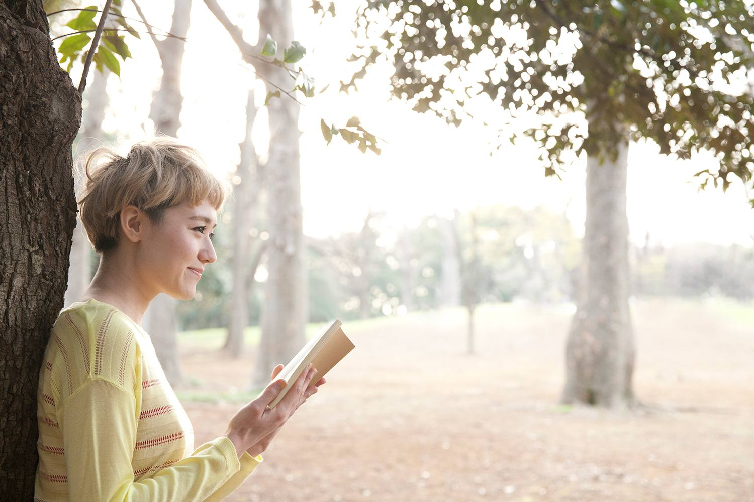 Fashionable Japanese woman reading book in park.