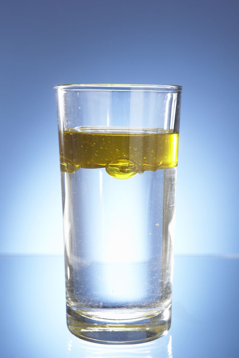 Oil floating on top of water in a glass