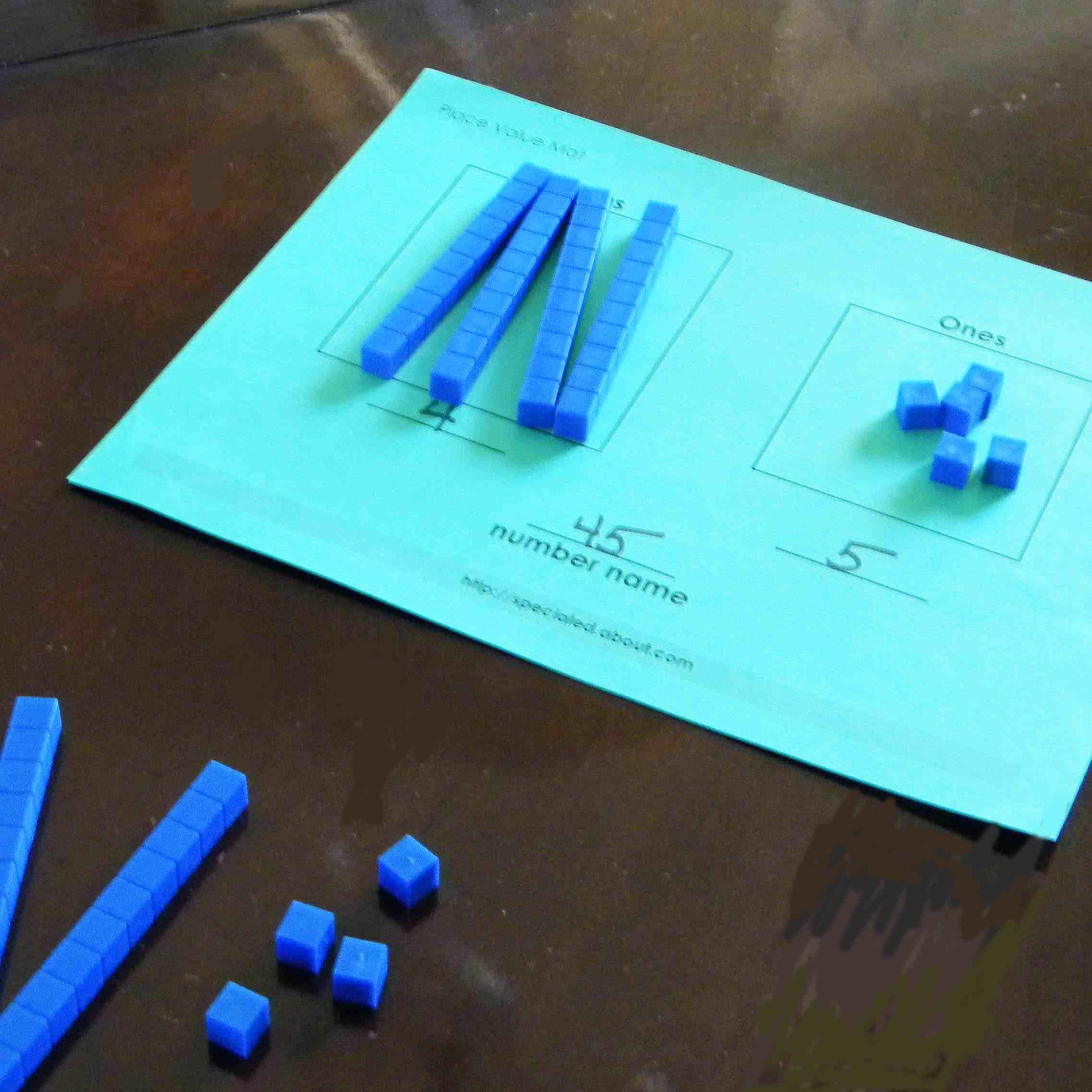 Place value sticks and worksheet on a student desk.