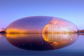 modern oval structure at dusk, reflected in a pool of water