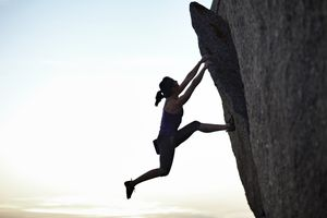A rock climber hanging from the side of a cliff