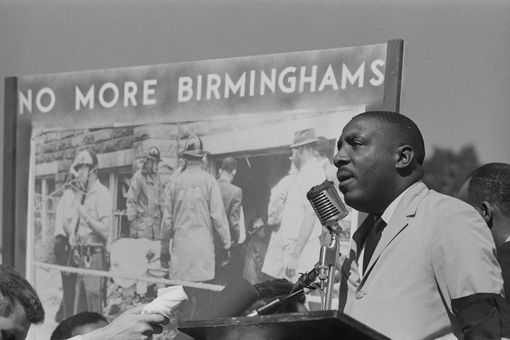 Comedian and activist Dick Gregory addresses a civil rights demonstration in Washington, DC. Behind him is a poster reading 'No More Birminghams', in reference to the bombing of the 16th Street Baptist Church in Birmingham, Alabama, by white supremacists.