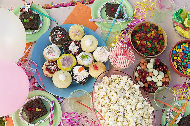 Party table with cupcakes, popcorn, and candies