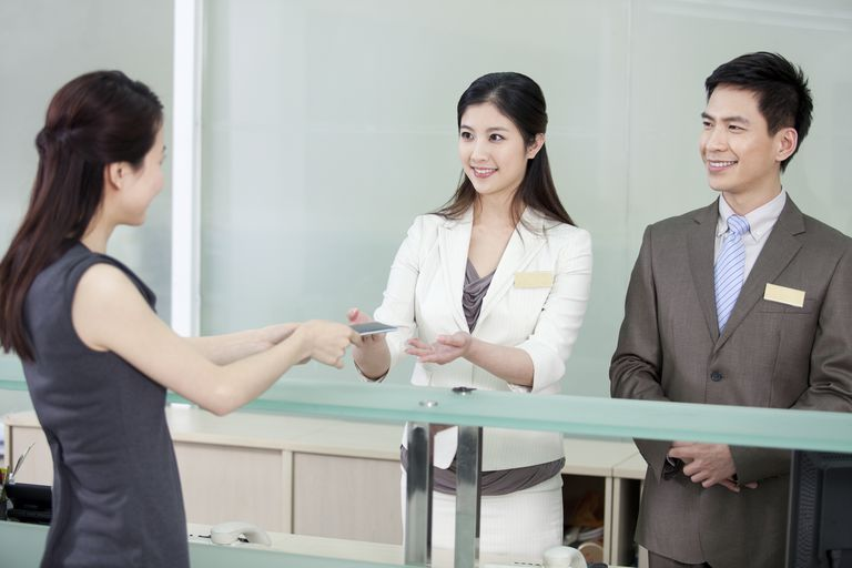 Businesswoman check in at reception desk, Beijing, China