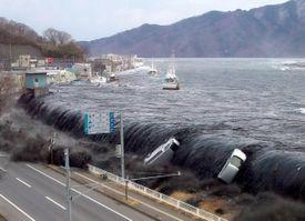 tsunami breeching an embankment and flowing into the city of Miyako, Japan