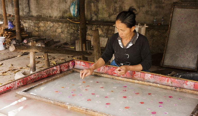 Woman placing petals in handmade paper.