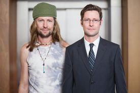 same guy side-by-side, one in a hat with long hair and one in a suit