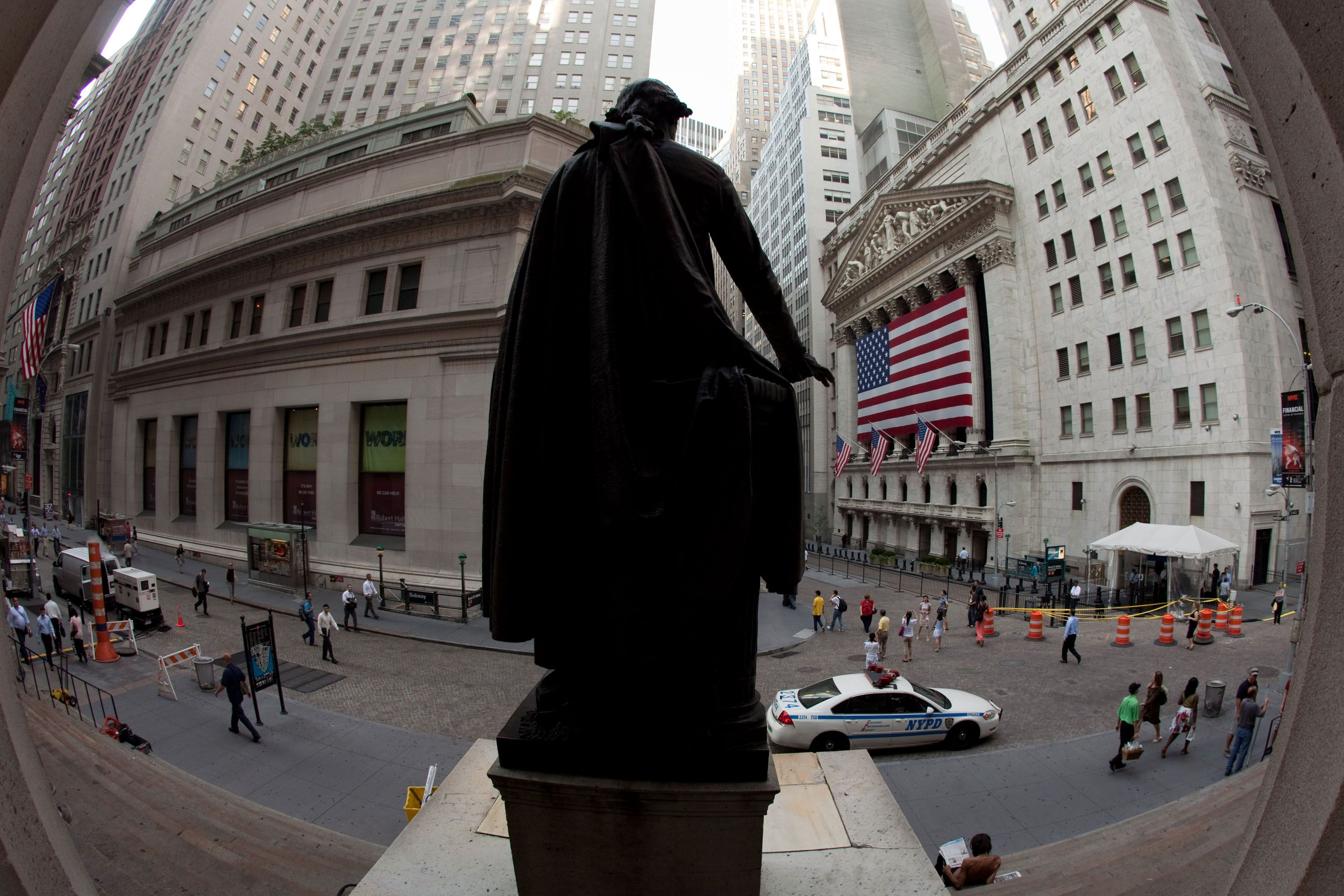 Behind a huge US flag covering the colonnade, the New York Stock Exchange facade is watched over by a statue of George Washington on Wall Street.
