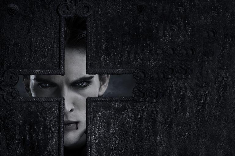Vampire standing behind cross