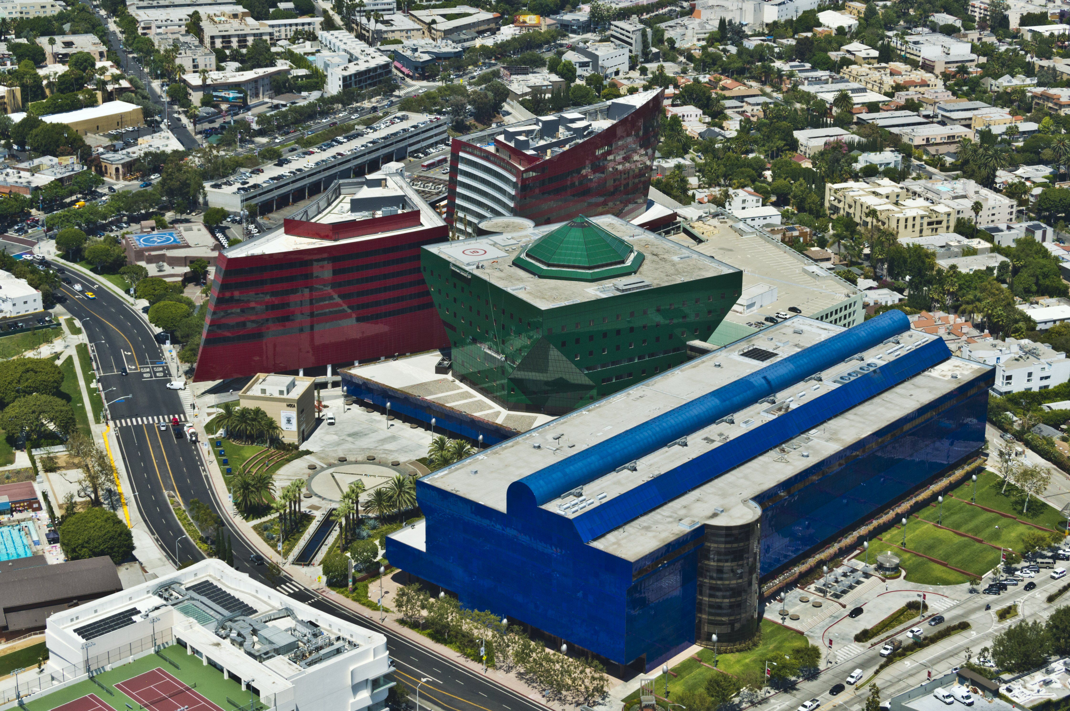 aerial view of three-building campus, a red building, green building, and blue building around a fountain and courtyard