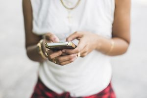A woman holds a cell phone in her hands.