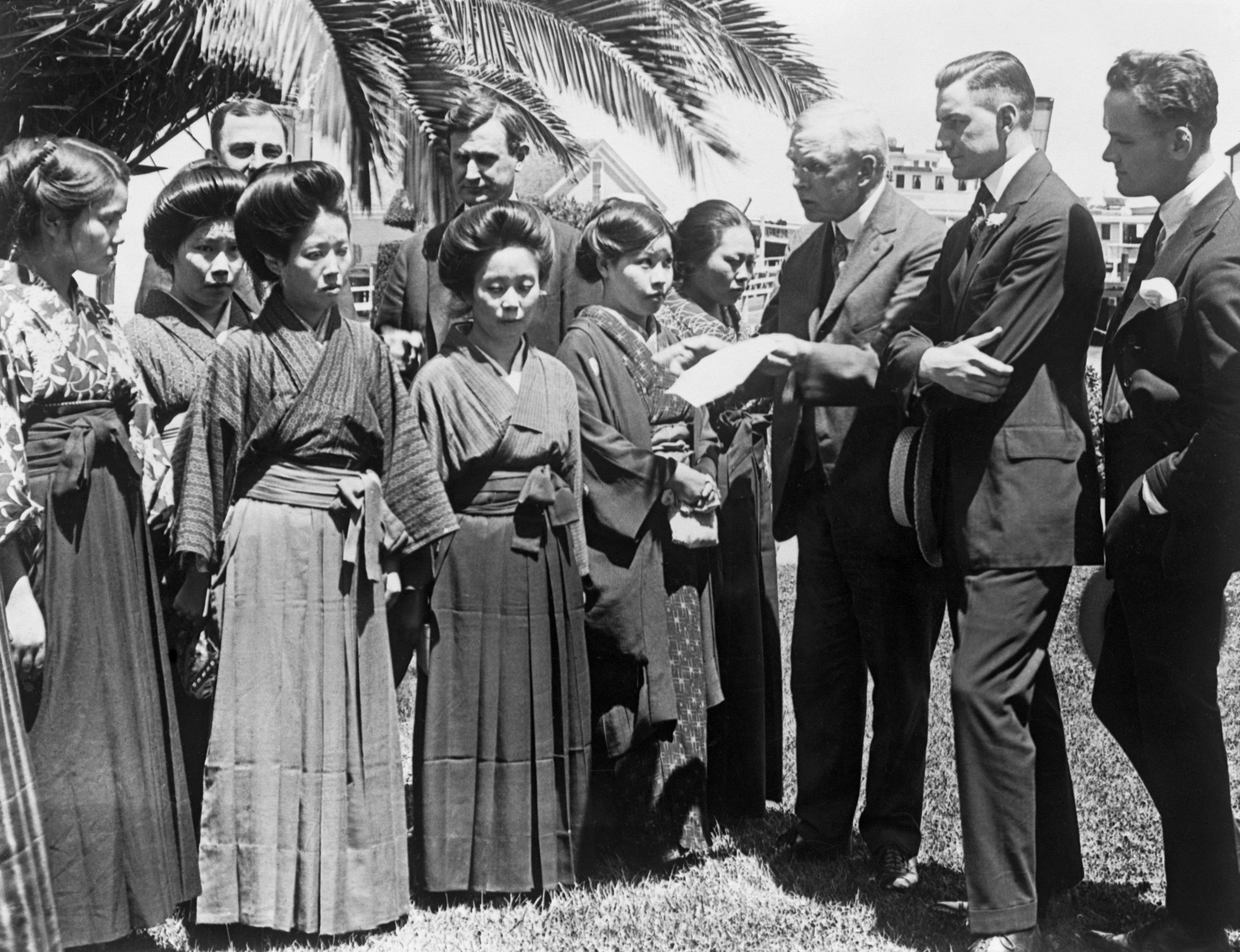 Members of a Congressional committee look over passports of Japanese immigrants