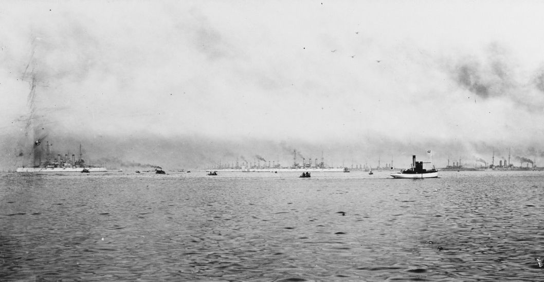Battleships of the Great White Fleet in port with with the Japanese fleet. Small craft in the foreground.