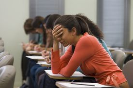 Students taking written examination, woman holding hand to head
