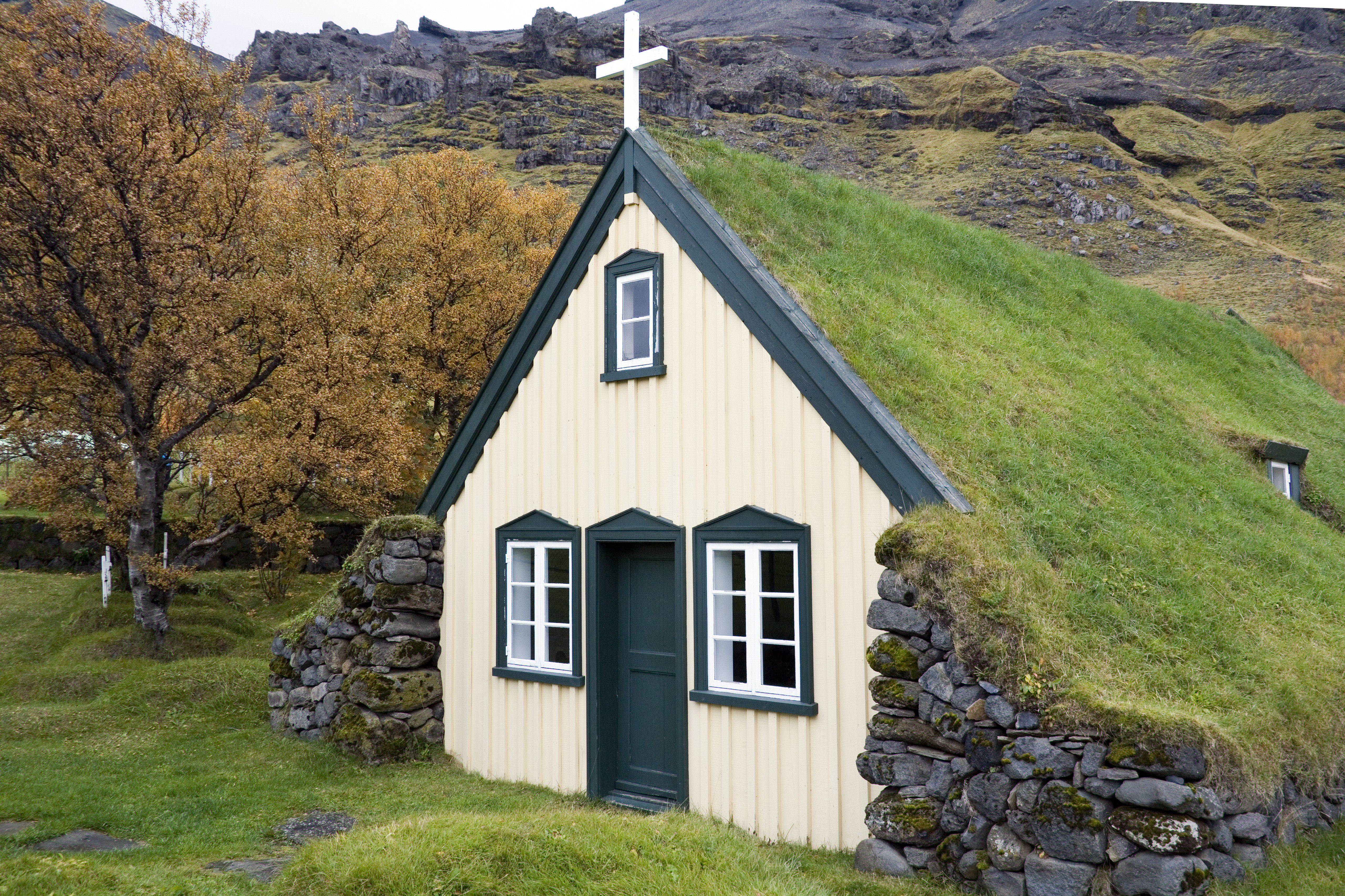 small, white church facade with sod gable roof