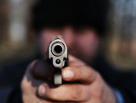Man pointing gun directly at camera
