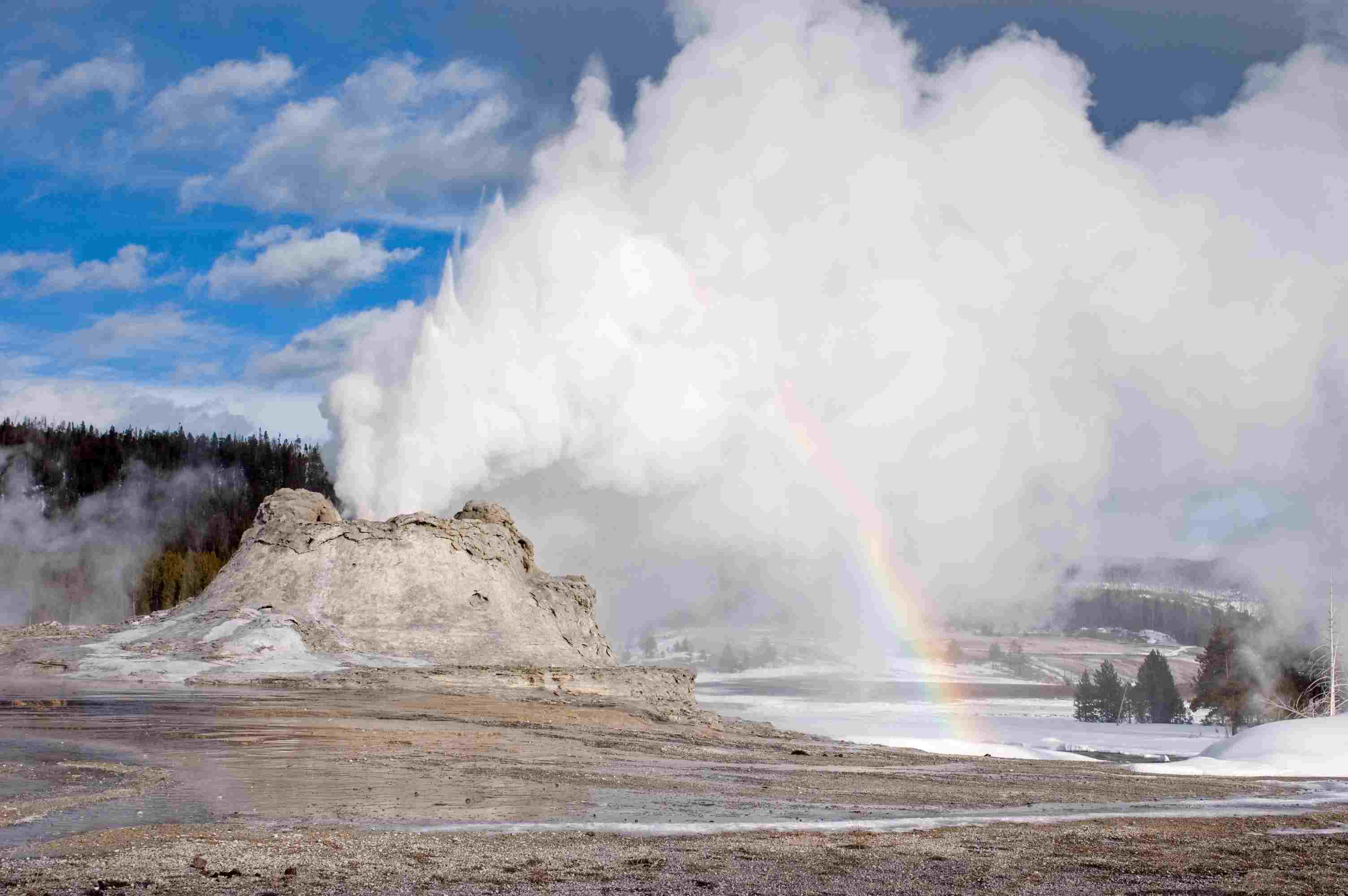 Castle Geyser Eruption with rainbow at Yellowstone National Park