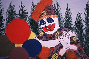 painting of a clown on backdrop of trees