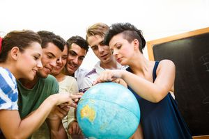 Teenagers searching place on a globe.