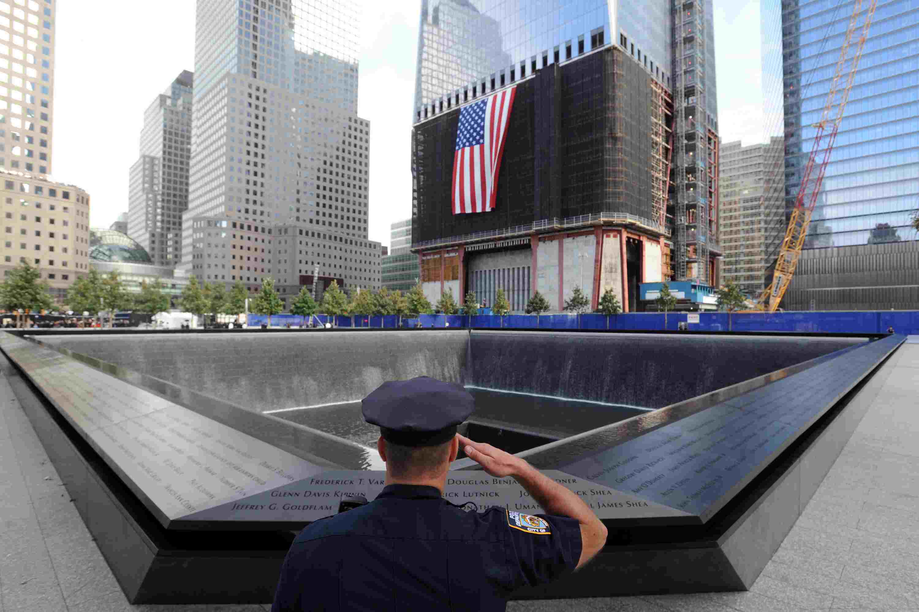 New York City Police Danny Shea Agent, un vétérinaire militaire, salue à la piscine nord du 9/11 Memorial lors de la cérémonie dixième anniversaire des attentats du 11 Septembre, attentats terroristes de 2001 sur le site du World Trade Center, le 11 Septembre, 2011 à New York ville, construction 1WTC en arrière-plan