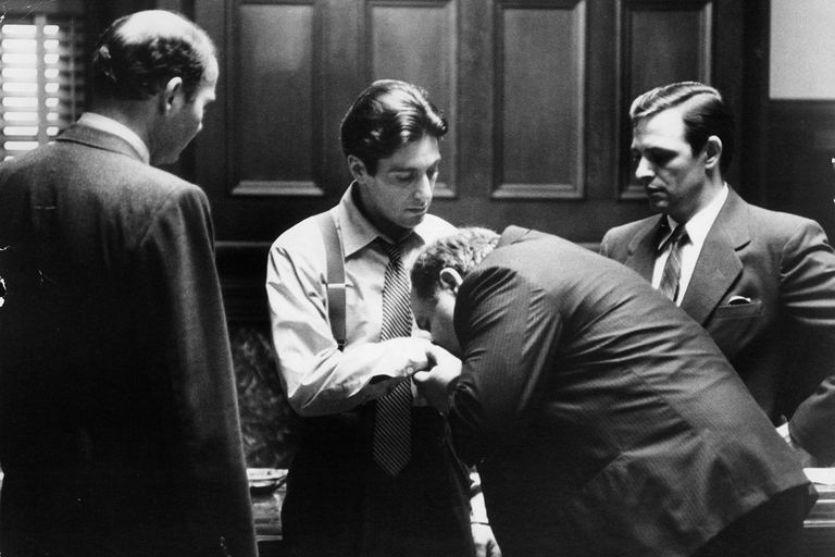 Still from The Godfather Part II depicting Clemenza kissing Michael Corleone's hand