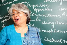 cheerful Indian professor in front of chalkboard
